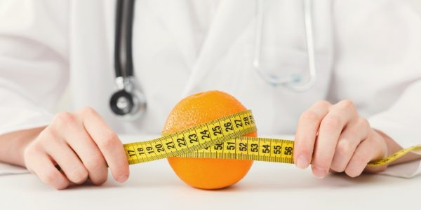 nutritionist-doctor-with-fruit-and-measuring-tape.jpg